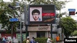 人们骑着摩托车路过的泰国爆炸案嫌疑人的数字广告牌( 2015年8月23日)。