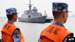 一艘新加坡海军舰艇抵达中国南部广东省湛江市的一个军事港口时,中国水手在一旁观看。(2018年10月21日)