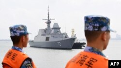This photo taken on Oct. 21, 2018 shows Chinese sailors watching as a Singapore navy ship arrives at a military port in Zhanjiang, in Guangdong province. China and Southeast Asian states will hold their first joint maritime exercises this week, officials.