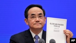 Xu Lin, Vice head of the Publicity Department of Communist Party, shows a copy of the white paper on fighting COVID-19 China during a press conference at the State Council Information Office in Beijing, June 7, 2020.
