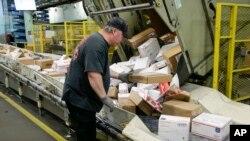 A U.S. postal worker arranges packages on a conveyor belt at the main post office in Omaha, Nebraska, Dec. 14, 2017.