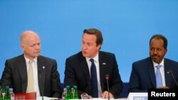 PM Inggris David Cameron (tengah) duduk di antara Menlu Inggris William Hague (kiri) dan Presiden Somalia Hassan Sheikh Mohamud, dalam Konferensi terkait pembangunan kembali Somalia di London (7/5).