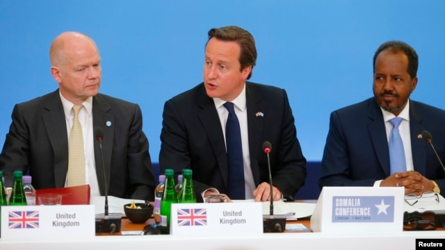 Britain's Prime Minister David Cameron (C) sits with Foreign Secretary William Hague (L) and Somali President Hassan Sheikh Mohamud, as he speaks at the Somalia conference in London, May 7, 2013.