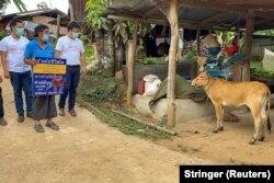 Charan Damrongkiatpana menunjukkan poster setelah memenangkan undian dalam program vaksinasi berhadiah sapi untuk meningkatkan vaksinasi COVID-19 di Provinsi Chiang Mai, Thailand, 8 Juni 2021. (Foto: Stringer/Reuters)