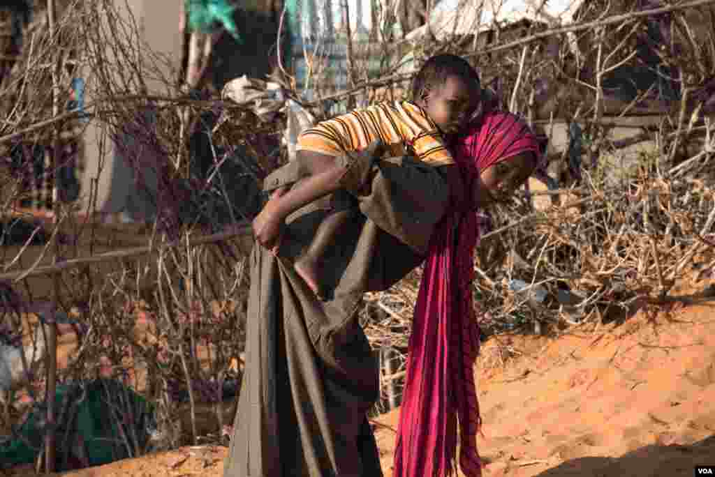 A girl carries a baby boy in a camp in Kismayo, Somalia that is home to both displaced Somalis and returned refugees on September 27, 2016. (J. Patinkin/VOA)