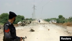 A policeman stands guard at the site of a roadside bomb outside Dera Ismail Khan, northwest Pakistan, Aug. 4, 2014.