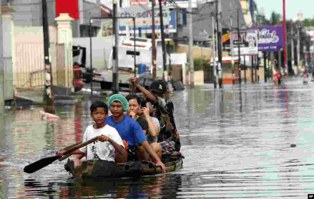 Cư dân miền bắc Jakarta, Indonesia dùng thuyền tre để di chuyển sau khi đường phố bị lụt. Các giới chức đã giảm nhẹ lời tiên đoán rằng mưa lớn và thủy triều cao vào ngày rằm có thể gây ra lũ lụt tệ hại nhất trong 6 năm qua. (AP)