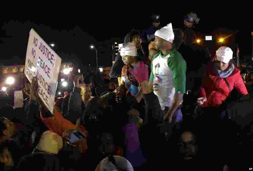 Bà Lesley McSpadden, mẹ của Michael Brown (trái) đứng trên nóc xe khi lắng nghe thông báo về quyết định của bồi thẩm đoàn tại Ferguson, Missouri, ngày 24/11/2014.