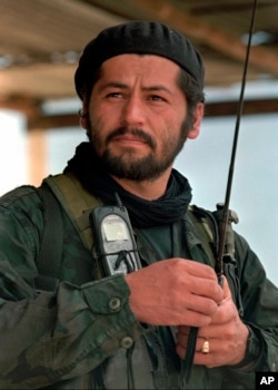 FILE - Henry Castellanos, also known as Romana, a senior commander of the Revolutionary Armed Forces of Colombia, talks on the radio in El Calvario, Colombia, March 27, 1998.