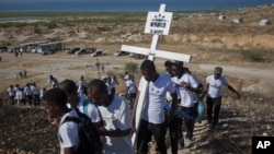 Relatives of those who died in the 2010 earthquake walk to place a cross on a hilltop to remember those who died in the devastating earthquake atTitanyen, a mass burial site north of Port-au-Prince, Haiti, Jan. 12, 2013.
