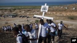 1月12日,2010年海地大地震遇难者的亲属前往海地太子港的一个大型墓地悼念亲人