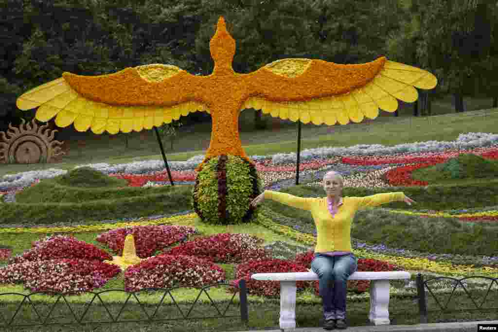 A visitor poses for a picture at a flower exhibition in Kyiv, Ukraine.