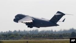 A C-17 cargo plane loaded with humanitarian commodities takes off from Homestead Air Reserve Base in route to Venezuela, Saturday, Feb. 16, 2019, in Homestead, Fla.