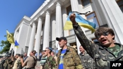 Maidan self-defense activists shout slogans in front of the Ukrainian parliament building in Kyiv on July 1, 2014.