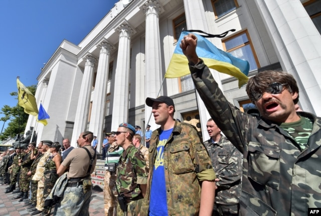 FILE - Maidan self-defense activists shout slogans in front of the Ukrainian parliament building in Kyiv on July 1, 2014, as they call for the ratification of an agreement with the European Union.