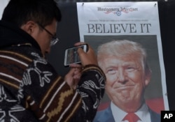 FILE - Zheng Gao of Shanghai, China, photographs the front pages of newspapers on display outside the Newseum in Washington, Nov., 9, 2016, the day after Donald Trump won the presidency.