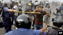 Police officials wield bamboo sticks to stop main opposition Bangladesh Nationalist Party activist during a protest in Kachpur, on the outskirts of Dhaka, December 9, 2012.