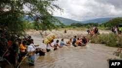 Les migrants utilisent une corde pour traverser le fleuve Tachira, la frontière naturelle entre la Colombie et le Venezuela, car la frontière officielle reste fermée en raison de la pandémie COVID-19 à Cucuta, Colombie, 19 novembre 2020.