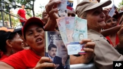 FILE - Pro-government supporters cheer as some hold up new banknotes and patriot identification cards during a rally in Caracas, Venezuela.