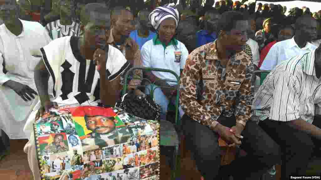 Des posters à l'effigie de Thomas Sankara sont vendus comme de petits pains sur la place des martyrs dans le quartier Tampouy dans le nord-ouest de Ouagadougou où plusieurs milliers de personnes se sont réunies pour commémorer le 28eme anniversaire de l'assassinat de Thomas Sankara, le père de la révolution burkinabè mort le 15 octobre 2015. (VOA/Bagass Kourai)