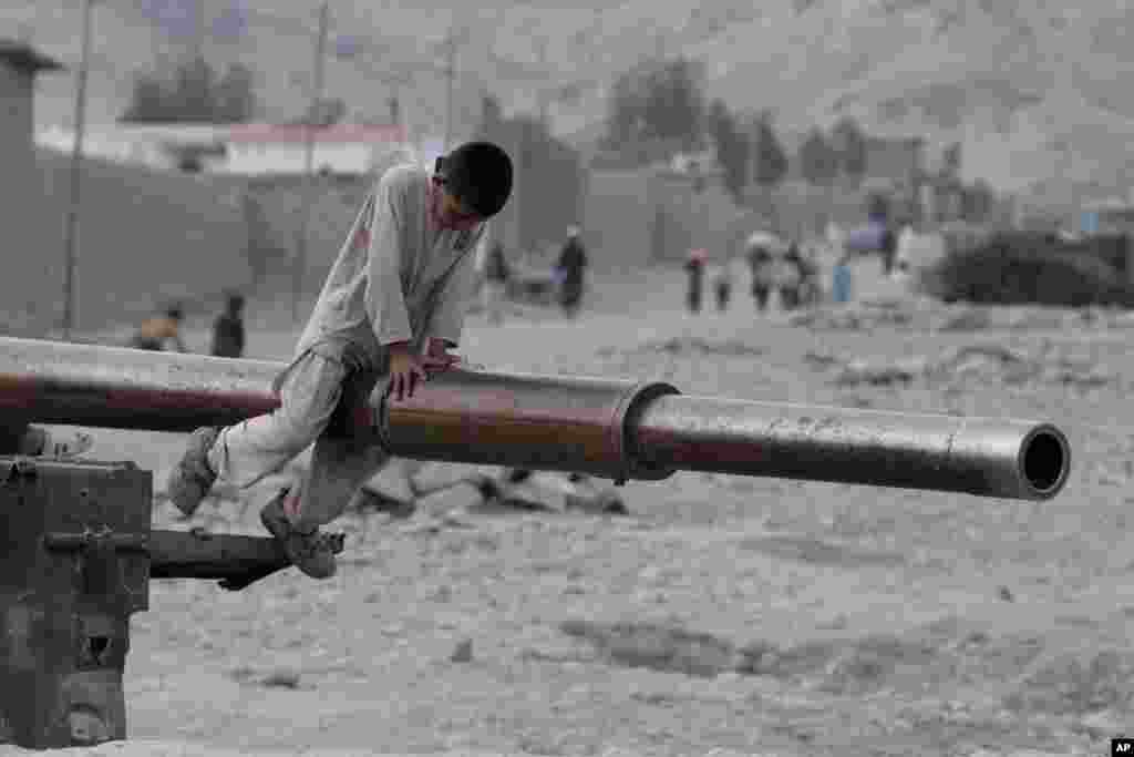 An Afghan child plays on the barrel of a Soviet tank in the Behsood district of Jalalabad, Afghanistan.