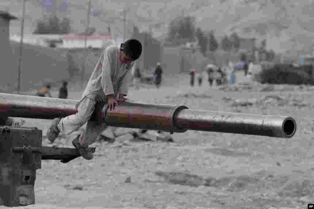 Seorang anak Afghanistan bermain dengan bekas tank Uni Soviet di distrik Behsood, kota Jalalabad, Afghanistan.