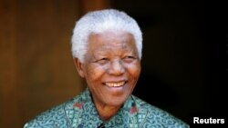FILE - Former South African president Nelson Mandela smiles for photographers at his home in Johannesburg on September 22, 2005.