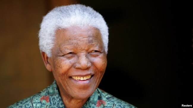 FILE - Former South African president Nelson Mandela smiles for photographers at his home in Johannesburg September 22, 2005.
