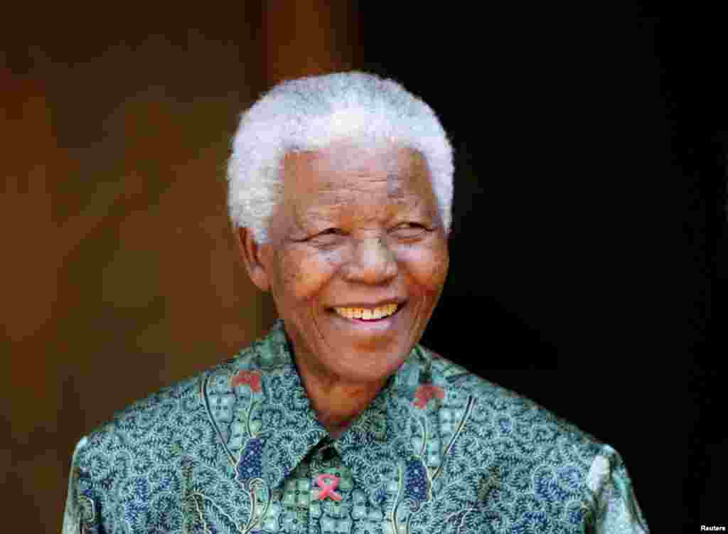 Nelson Mandela smiles for photographers at his home in Johannesburg September 22, 2005.