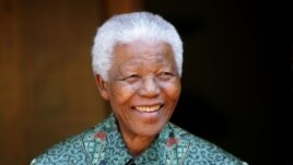 FILE - Former South African president Nelson Mandela smiles for photographers at his home in Johannesburg on September 22, 2005.