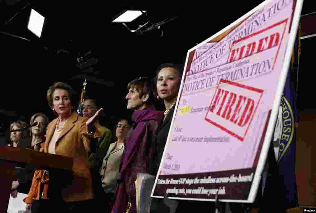在华盛顿国会山,众议院少数党领袖佩洛西(民主党籍-加州)指着一个标语牌,标语牌复制了一份因自动削减预算即将开始而把75万美国人解雇的通知。