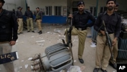FILE - Pakistani police officers stand guard at the office of local electrical company attacked by angry protesters to condemn electricity shortages in Lahore, Pakistan, March 27, 2012.