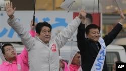 Pemimpin Partai Oposisi Jepang, partai Demokratik Liberal (LDP) Shinzo Abe (kiri) dan kandidar partai Yoshitaka Shindo melambaikan tangannya di hadapan para pendukungnya dalam kampanye untuk pemilu Parlemen Jepang, di Kawaguchi, dekat Tokyo, Sabtu (15/12). Pemilu parlemen akan dilaksanakan hari Minggu , 16 Desember 2012.