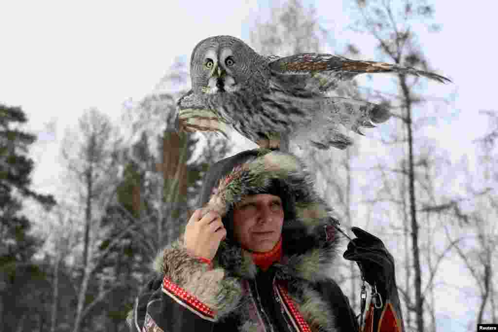 Mykh, a two-year-old Great Gray Owl, sits on the head of ornithologist Daria Koshcheyeva during a training session, which is part of a project of a local zoo to tame wild animals for further research and interaction with visitors, in the Siberian Taiga forest in Krasnoyarsk, Russia.