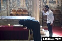 Serbs pray before the tomb of 'holy king' Stefan Dečanski.