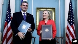 Secretary of State Hillary Rodham Clinton and Romania's Foreign Minister Teodor Baconschi shows the bilateral agreement between US and Romania on the deployment of Ballistic Missile Defense System in Romania.