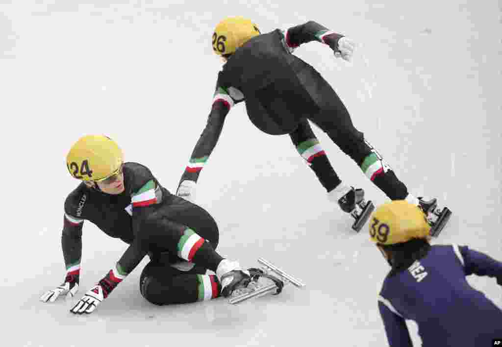 Arianna Fontana of Italy, left, crashes out in the women's 3000m short track speedskating relay final at the Iceberg Skating Palace during the 2014 Winter Olympics, Feb. 18, 2014.