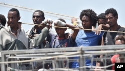Migrants wait to be disembarked from the Irish Navy ship P31 L.E. Eithne at the Catania harbor, Italy, June 16, 2015.