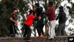 Người tị nạn ngăn cản một người toan nhảy xuống từ mái nhà Trung tâm tạm giam Villawood ở Sydney trong cuộc biểu tình vì lo sợ bị trả về nước.
