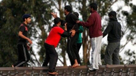Người tị nạn ngăn một tù nhân nhảy xuống khỏi mái nhà của Trung tâm giam giữ Villawood ở Sydney, Australia.