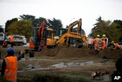 Workers dig graves at a Muslim cemetery in Christchurch, New Zealand, March 17, 2019, for victims of a mass shooing at two area mosques.