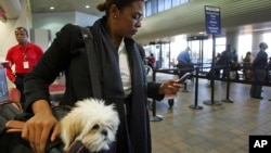 Milsa Grant of New York holds her dog Lulu Madonna, as she waits to check-in at LaGuardia Airport in New York. (File photo)