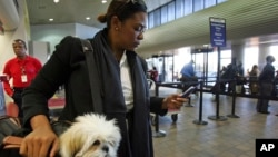 Milsa Grant of New York holds her dog Lulu Madonna, as she waits to check-in at the Delta terminal at LaGuardia Airport in New York. Apps can help plan and navigate new places and languages while you travel. (FILE, AP Photo/Dima Gavrysh)