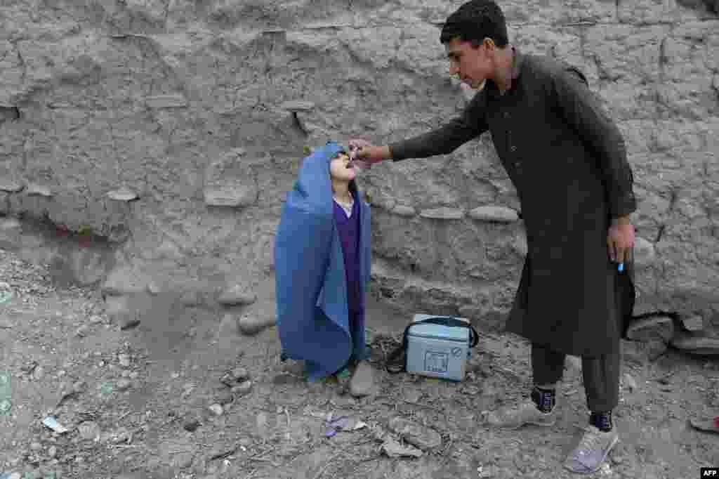 Seorang petugas kesehatan memberikan vaksin polio kepada seorang anak pada program vaksinasi pemerintah di pinggiran Jalalabad, Pakistan.