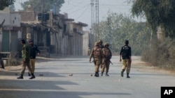 Cảnh sát và binh sĩ Pakistan canh gác trên con đường dẫn đến hiện trường vụ nổ bom ở Bannu, ngày 19/1/2014.