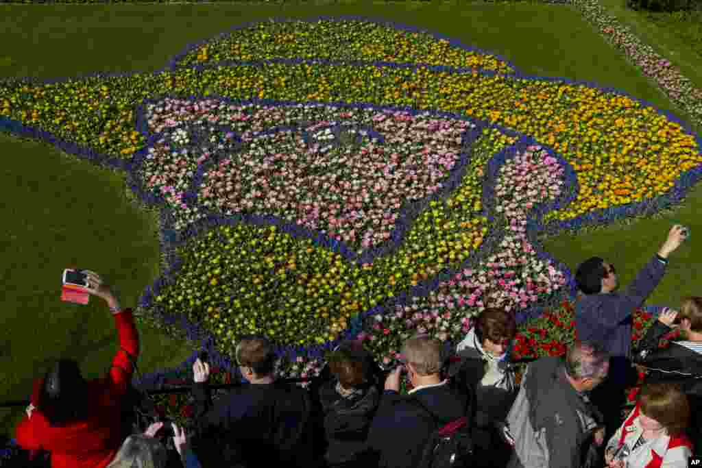 Tourists take pictures of a floral arrangement depicting Dutch master Vincent van Gogh at Keukenhof, a spring park with approximately seven million flower bulbs, in Lisse, Netherlands.
