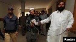 Cảnh sát Pakistan áp tải chỉ huy quân sự hàng đầu của phe Taliban Mullah Abdul Ghani Baradar.