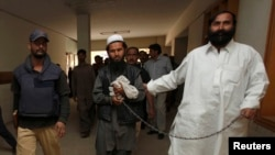 FILE - Police escort a man, identified as the Afghan Taliban's top military commander, Mullah Abdul Ghani Baradar.