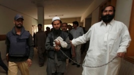 FILE - Police escort a man, identified as Afghan Taliban's top military commander, Mullah Abdul Ghani Baradar.