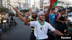Warga Palestina merayakan gencatan senjata dengan pawai keliling kota Gaza, Selasa (26/8).